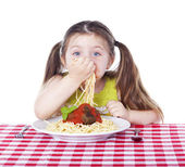 Beautiful girl eating pasta and meatballs with hands — Stock Photo