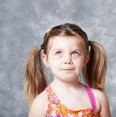 Cute little girl looking up towards copyspace — Stock Photo