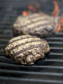 Hamburgers sizzling on the grill — Stock Photo