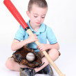 图库照片: Preschool boy looking down at bat