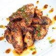 Stock Photo: Hot grilled chicken wings on white plate with drizzle of sauce