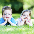 Siblings laying in the grass — Stock Photo