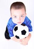 Young preschool boy laying on a soccer ball — 图库照片