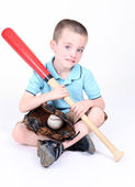 Young boy holding a baseball bat with ball and glove — Stock Photo