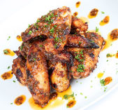 Hot grilled chicken wings on white plate with drizzle of sauce — Stock Photo