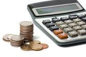 Pila di monete e calcolatrice isolato su bianco — Foto Stock
