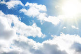 Blue sky with clouds and sun — Stok fotoğraf