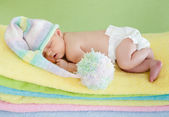 Newborn baby girl weared cap sleeping on colourful towels — Stock Photo