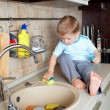 Adorable little boy washing sink on kitchen — Stock Photo