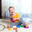 Funny child playing with color toy - Stock Photo