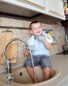 Śmieszne małe dziecko chłopiec mycie naczyń w kuchni — Zdjęcie stockowe