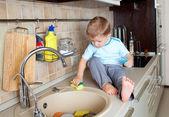 Bezaubernd kleiner Junge, die Spüle in der Küche waschen — Stockfoto