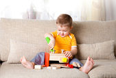 Adorable boy playing with wooden building toys at home — Stock Photo