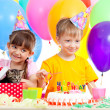 Happy children celebrating birthday party with opening gift box — Stock Photo #10413113