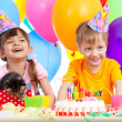 Happy children celebrating birthday party with opening gift box — Stock Photo