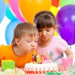 Kids celebrating birthday party and blowing candles on cake — Stock Photo