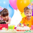 Happy children celebrating birthday party with opening gift box - Stock Photo