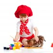 Small artist child painting with brush. Kitten looking girl — Stock Photo