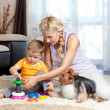 Mother, child boy and pet dog playing together indoor — Stock Photo #10661229