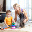 Mother, child boy and pet dog playing together indoor — Stock Photo #10661269