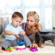 Mother, child boy and pet dog playing together indoor — Zdjęcie stockowe #10661296