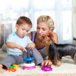 Foto Stock: Mother, child boy and pet dog playing together indoor