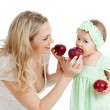 Mother and her child feed each other by red apples — Stock Photo