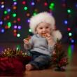 Funny baby in Santa Claus hat on bright festive background — Zdjęcie stockowe