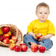 Child eating apple and basket — Stock Photo