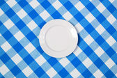 White round plate on blue checked tablecloth — Stock Photo