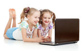 Smart tjejkompisar ler och tittar på den bärbara datorn — Stockfoto