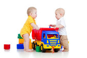 Two little childs playing with color toys and truck — Stock Photo