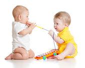 śmieszne dzieci bawiące się zabawki muzyczne. na białym tle na biały bac — Zdjęcie stockowe