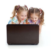 Two girls are smiling and looking at the laptop — Stock Photo