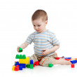 Little cheerful child playing with construction set over white b — Stock Photo #9442409