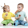 图库照片: Happy children little girl and boy with ice cream in studio isol