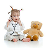 Adorable child with clothes of doctor and teddy bear over white — Foto Stock