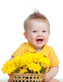 Laughing baby boy with flowers in basket — Stock Photo