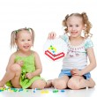 Foto de Stock  : Cute girls sisters playing together over white background