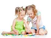 Elder sister training young one to collect mosaic toy over white — Stok fotoğraf