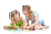 Elder sister training young one to collect mosaic toy over white — Stock Photo