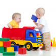 Two little children playing with color toys - Stock Photo