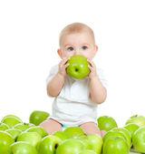 Adorable baby sitting among fresh fruits and eating green apple. — Stock Photo