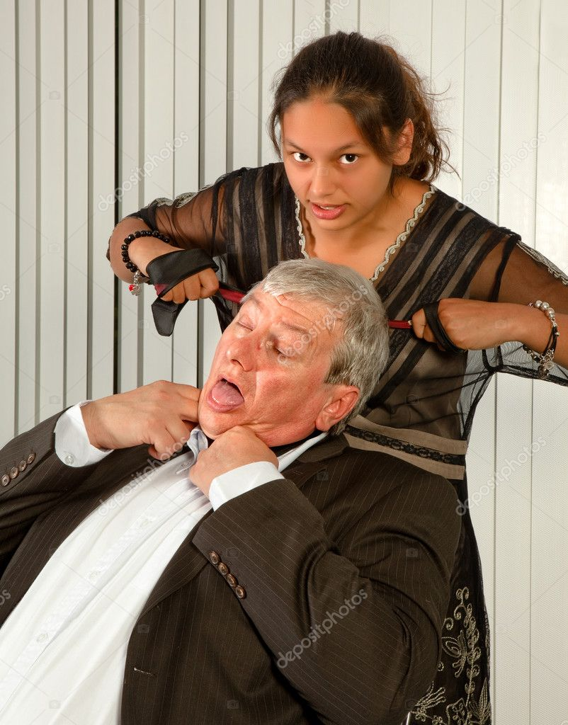 Office worker or secretary strangling her boss with his own tie  Stock Photo #10050422