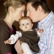 Couple kissing baby — Stock Photo
