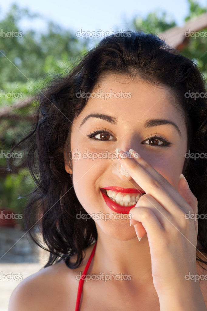 Pretty young woman putting sunscreen cream on her nose — Stok fotoğraf #10381849