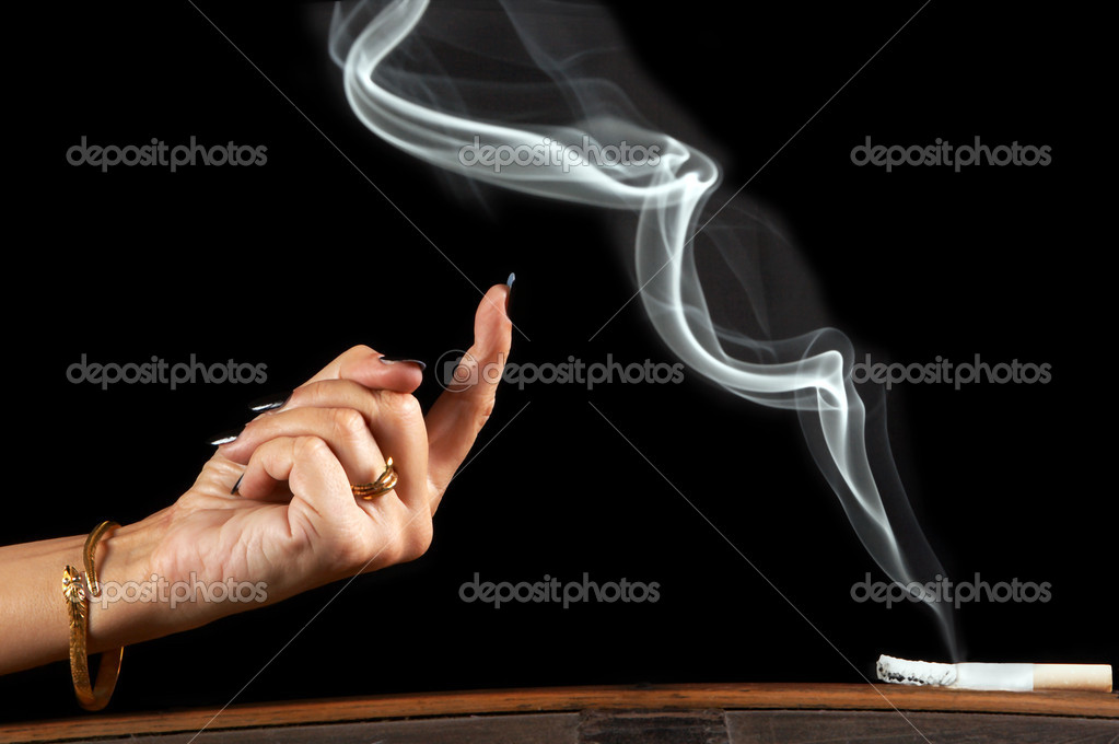 Woman's hand beckoning a wisp of smoke of a sigarette  Stock Photo #10403764