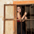 Sad woman behind bars — Stockfoto