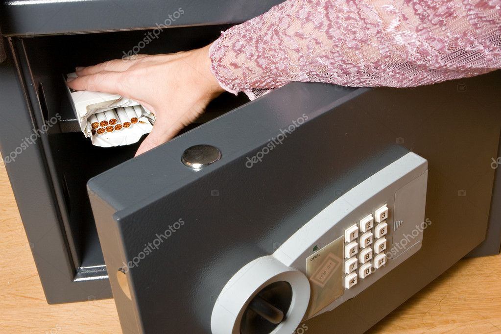 Hand trying to take cigarettes out of the safe — Stock Photo #8737661