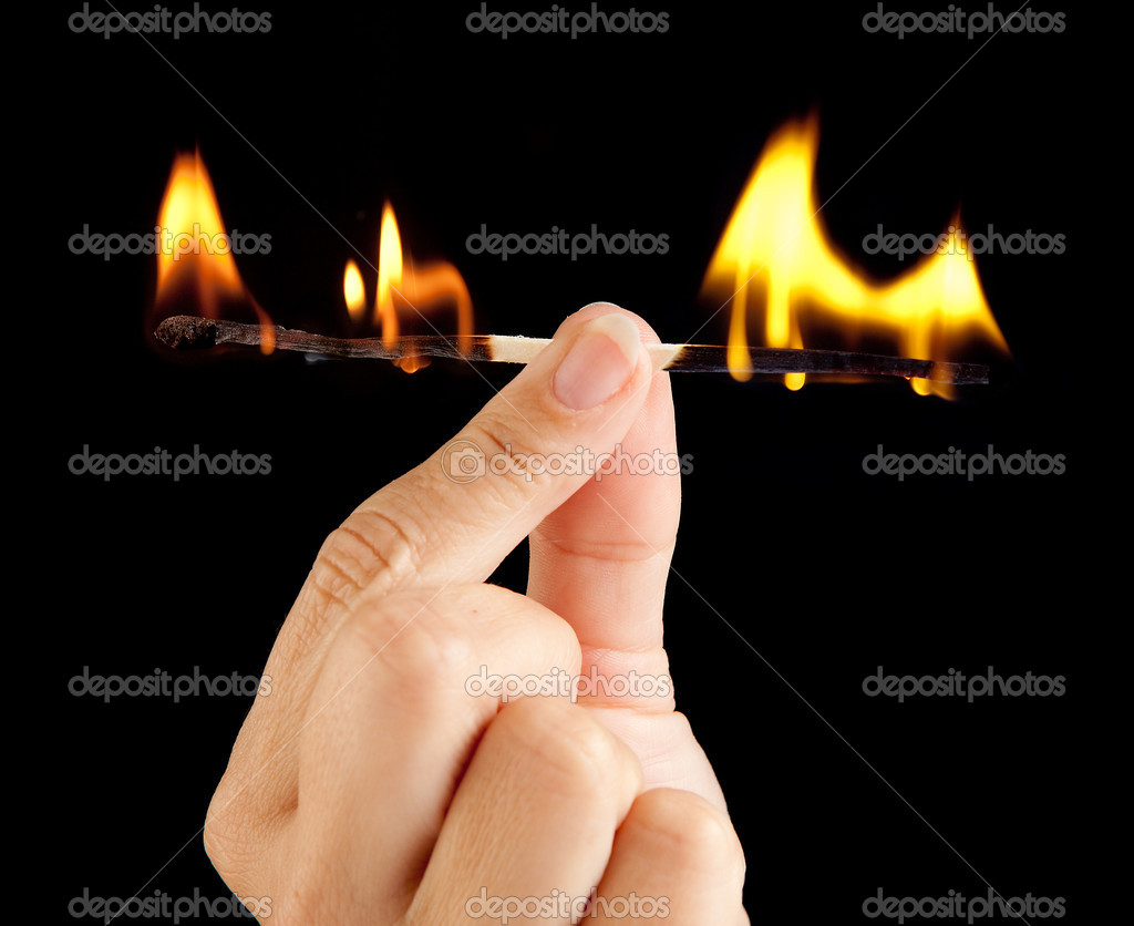 Hand holding a match burning at both ends  Stok fotoraf #8738032
